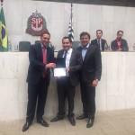 Eduardo Martins recebe a homagem das mãos de Capez e Pesaro (Foto: Divulgação)
